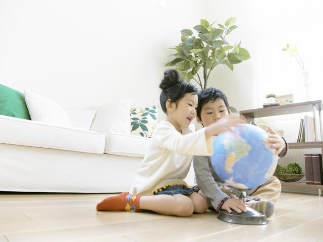 地球儀を見ている姉弟